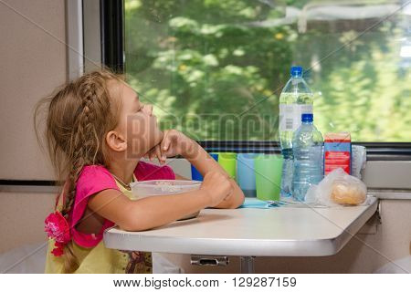 A Six-year Girl In A Train Sitting At A Table With Food On A Lower Place In The Second-class Compart