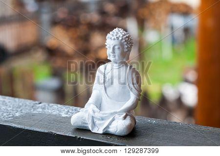 Image of sitting Buddha on blurred background. Meditation concept.