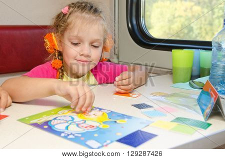 A Small Child In A Train Of Fun Playing At The Table At The Lower Place In The Second-class Compartm