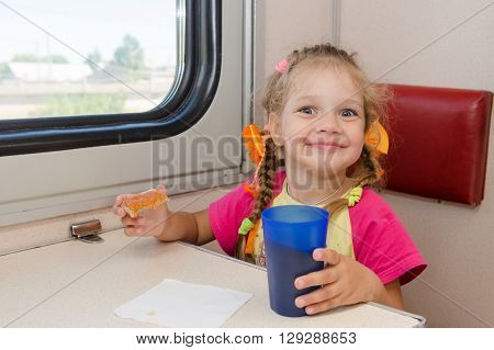 Little Girl With A Happy Face Drink Tea With A Sandwich On The Train At The Table On Outboard Second