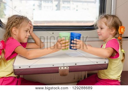 Two Little Sisters In Identical Pajamas Drinking Tea In The Train At The Table On Outboard Second-cl
