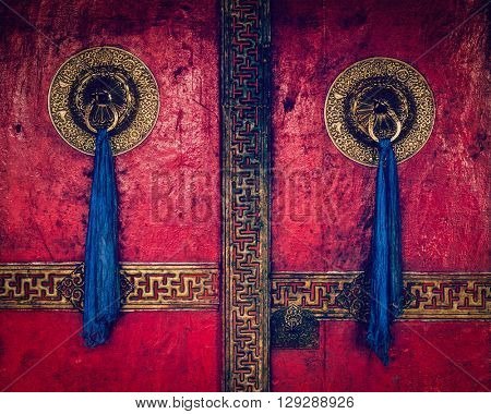 Vintage retro effect filtered hipster style image of gate of Spituk Gompa (Tibetan Buddhist monastery) with ornamented decorated door handles. Ladakh, India