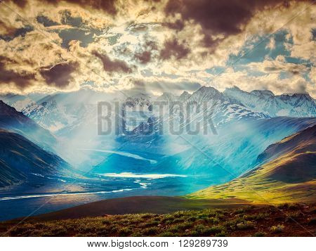 Vintage retro effect filtered hipster style image of Himalayan valley landscape with Himalayas mountains. Sun rays come through clouds. Himachal Pradesh, India