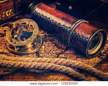 Travel geography navigation concept background - vintage retro effect filtered hipster style image of old vintage retro compass with sundial, spyglass and rope on ancient world map