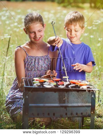 Children grilling vegetable. Family camping and enjoying BBQ. Brother and sister at barbecue preparing healthy vegetable meal outdoors.