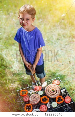 Boy grilling vegetable. Family camping and enjoying BBQ. Cute boy at barbecue preparing healthy vegetable meal outdoors.