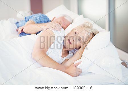 Shocked senior woman sleeping besides man on bed in room