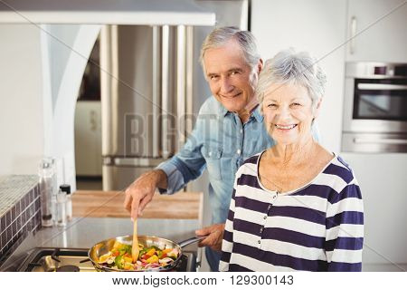 Portrait of senior couple cooking food in kitchen