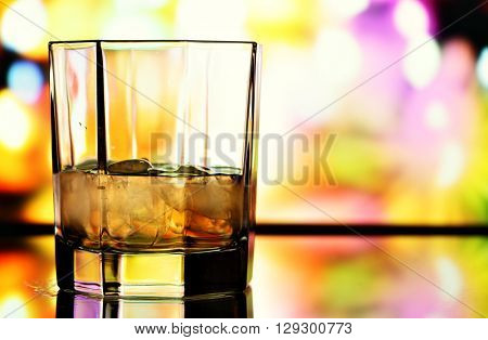 Glass of whiskey over colorful background