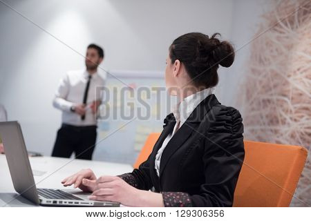 young business woman on meeting usineg laptop computer, blured group of people in background at  modern bright startup office interior taking notes on white flip board and brainstorming about plans