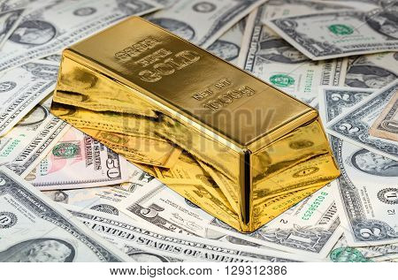 gold bar close-up on a background of dollar bills