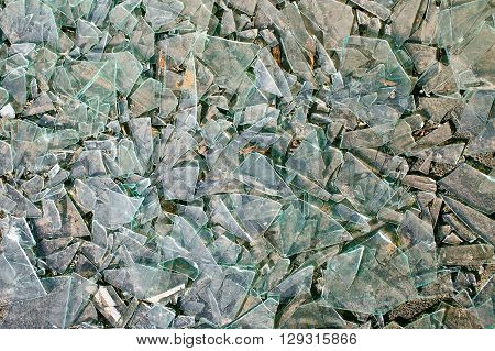 broken glass lies on the rocks. background of the fragments of window glass on the ground. closeup