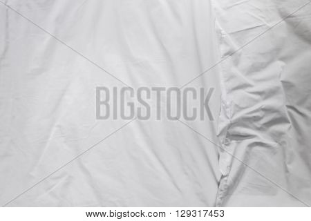 Top view of white bed sheets and pillow crease