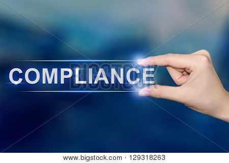 hand pushing compliance button on blurred blue background
