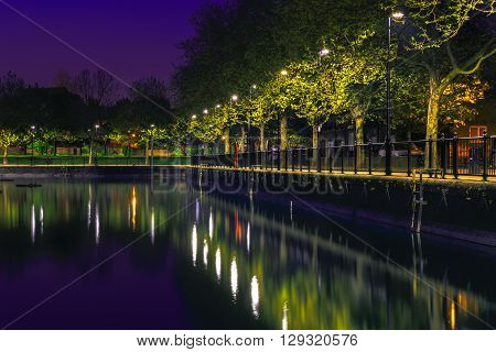 Row of lampposts and their reflection from Surrey Water in London after sunset