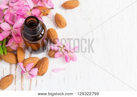 Background with almond oil almonds and flowers.
