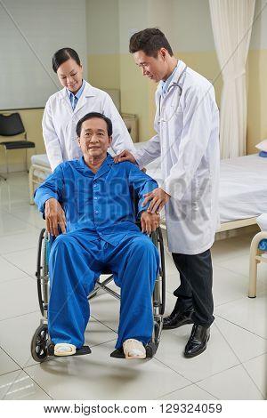 Vietnamese doctor and nurse reassuring handicapped senior man