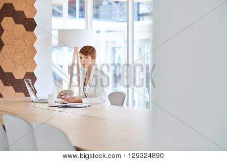 Young busineswoman looking away with a serious and thoughtful expression while sitting at a desk in a bright modern office