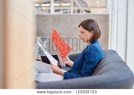 Attractive busineswoman sitting on her office couch and looking at various paperwork documents with a serious expression