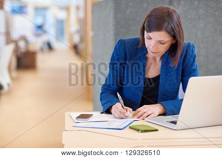 Stylish young busineswoman writing while working on paperwork at her desk in a bright shared office with a cucbicle divider behind her
