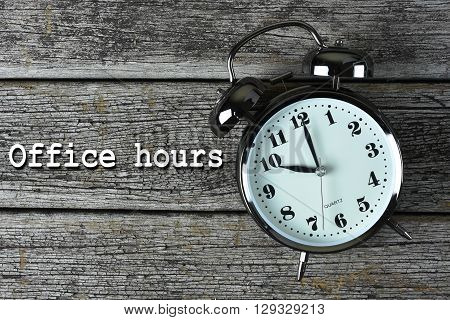 Black alarm clock on the rusty wooden table with word Office hours