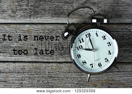 Black alarm clock on the rusty wooden table with word It is never too late