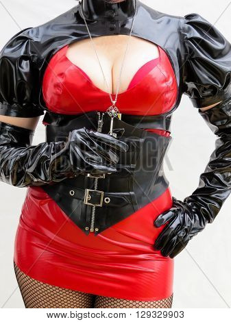 Close up of dominatrix body in a red and black PVC outfit holding a key
