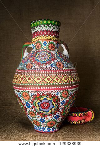 A colorful Egyptian handcrafted artistic ornate pottery jar on a sackcloth background. one of the art works of Ebtessam ElGohary a contemporary Egyptian artist specialized in pottery painting art. Decorations are inspired by the Mandala style