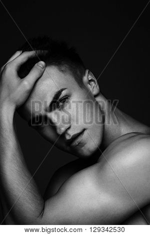 Fashion man portrait with his hand in his hair on dark background black and white photo