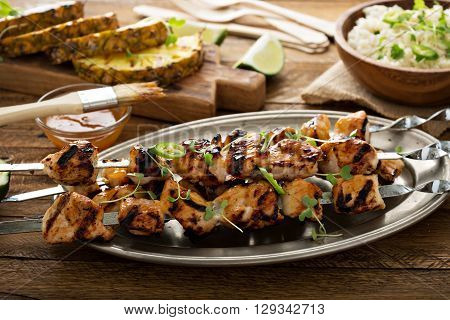 Chicken kabobs with sweet and sour sauce on metal skewers