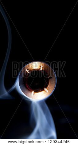 Copper colored hollow point bullet and smoke pointed at the camera