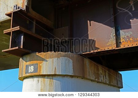 An old railroad bridge utilizes riveted steel girders resting on concrete bents (piers) and is still in service today.