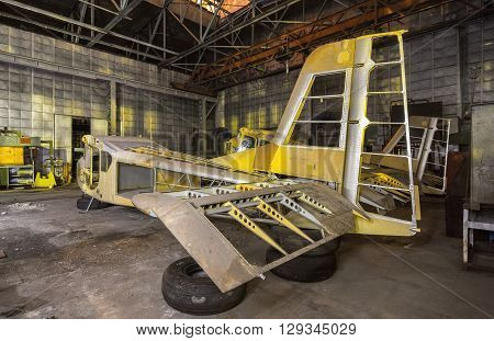 Abandoned aviation factory of small aircraft . The partially-built airplane in a dark industrial building at night. Focus on the tail of plane