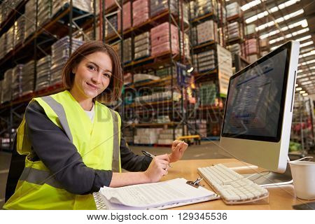 Woman working in the office of a warehouse looks to camera