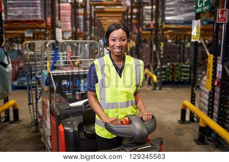 Woman operating a tow tractor in a warehouse looks to camera