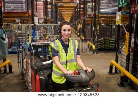 Young woman operating tow tractor in distribution warehouse