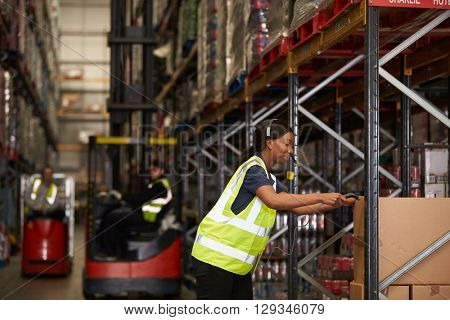 Woman working in a warehouse scans box with a barcode reader