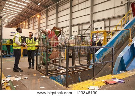 Warehouse manager and colleague talk by recycling machinery