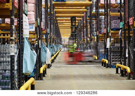 Forklift driving across an aisle in a warehouse, motion blur