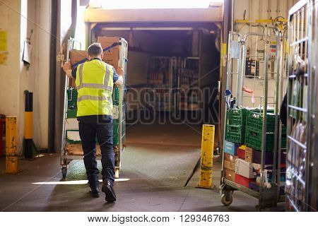 Man pushing roll cage into a truck at a warehouse, back view
