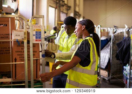 Woman prepares roll cage for delivery, checked by supervisor
