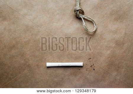 concept hangman's knot on kraft paper background with cigarette close up