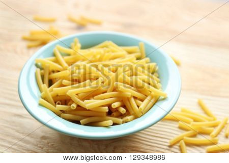 Dry maccheroni pasta in blue plate on wooden table