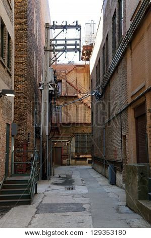 A narrow alleyway between tall buildings in downtown Joliet, Illinois.