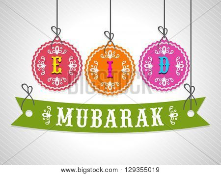Colourful hanging Tags and Ribbon with stylish text Eid Mubarak on shiny grey background for Muslim Community Festival celebration.