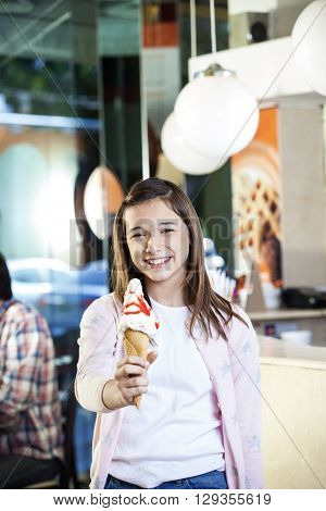 Smiling Preteen Girl Holding Vanilla Ice Cream At Parlor