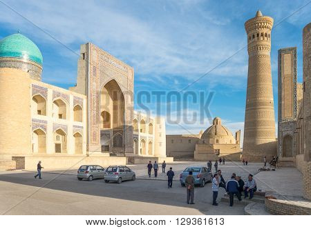 Buckara Uzbekistan - Aprilr 16 2014: Local people in the square with the Mir-i-Arab madrassah and the Kalon mosque in the background