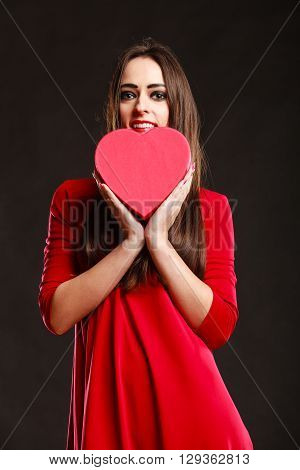 Charity and sharing concept. Young pretty woman in red clothes holding heart box present gift on grey background in studio.