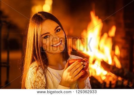Happy joyful woman drinking cup of coffee relaxing at fireplace. Young girl with hot beverage heating warming up. Winter at home.