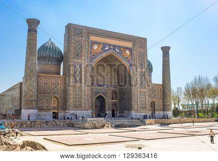 Samarkand Uzbekistan - April 18 2014: People around the Sher Dor madrassah in Registan square